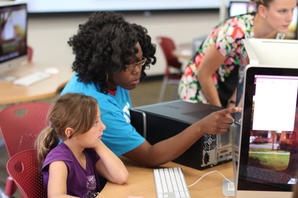 FITC Student Ambassador Ania Aus assists one Girl Scout during the Game Design workshop